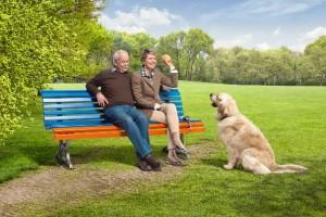 Älteres Paar sitzt auf Bank und spielt mit Hund