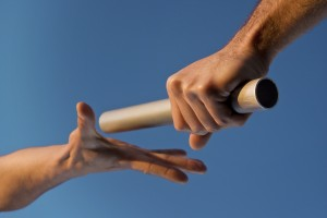 Low angle close-up of two hands passing a relay baton, with focus on the hand holding the baton, against a clear blue sky. Warm tones highlight the fact that the image was shot at sunset. Horizontal format.