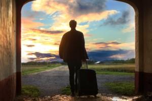 Mann mit Rollkoffer geht Richtung Sonnenuntergang