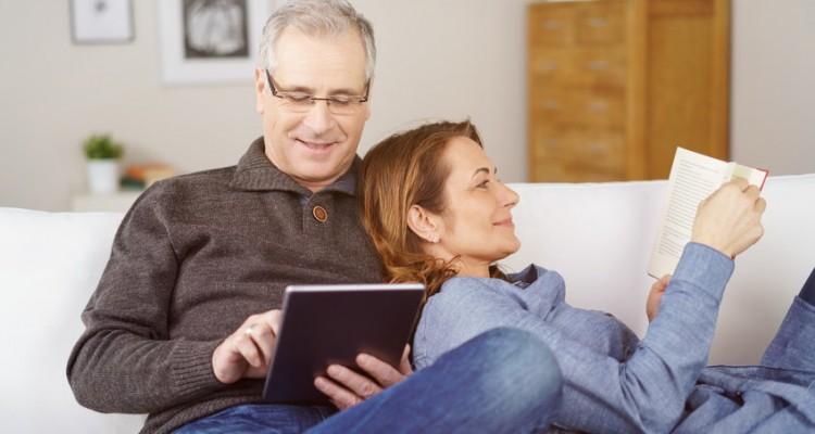 Paar liegt gemütlich auf dem sofa mit tablet und buch