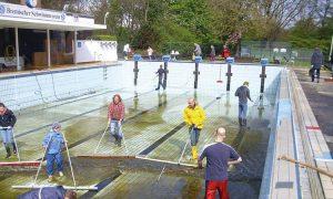 Helfer reinigen ein Schwimmbecken im Außenbereich
