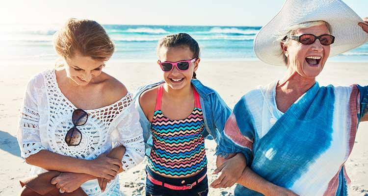 Drei-Generationen-Bild: Eine ältere Frau, eine Frau mittleren Alters und ein Mädchen am Strand