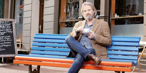 Mann mittleren Alters sitzt mit einer Tasse Kaffee auf der Bank