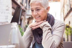 Frau mittleren Alters sitzt vor einem Laptop.
